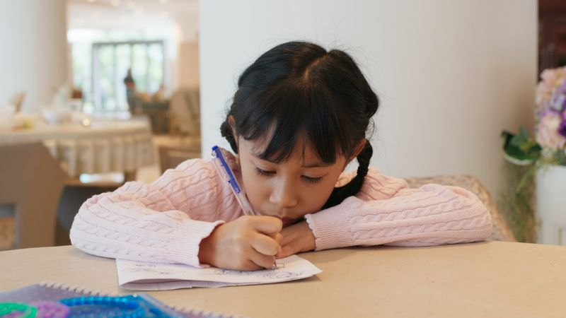 girl drawing at a table